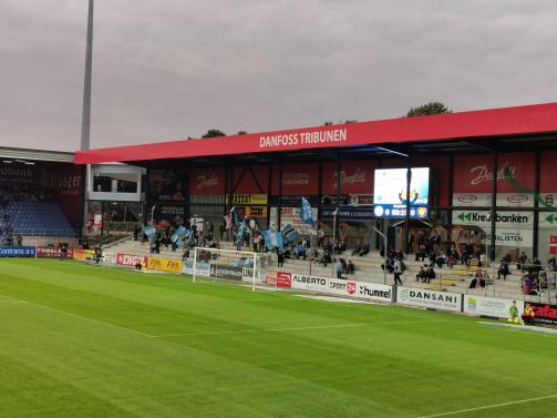 © Lennart Fey / Sitzende SønderjyskE-Ultras auf der Stehplatztribüne